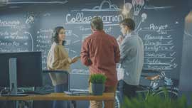 a group of people discussing about brainstorming ideas written on a blackboard